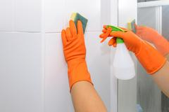 Man doing chores in bathroom at home, cleaning wall with spray detergent Stock Photos
