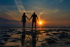 Couple hand in hand towards the sea in a dawn late summer Stock Photos