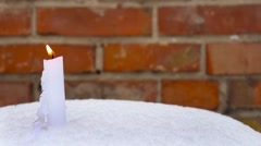 Candle on snow against brick wall. Christmas holidays background Stock Footage