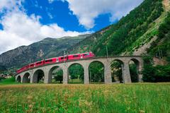 Swiss mountain train Bernina Express Cross the bridge in the circle to gain a Stock Photos