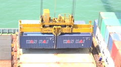 A gantry crane or portainer is stacking containers on a large ship. 4K Stock Footage