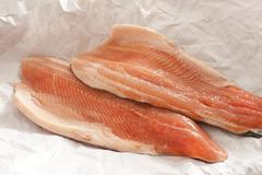 Two trout fillets displayed on paper Stock Photos