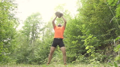 Men Lifts A Heavy Stone. Man Running Cross Country In Summer Forest. Stock Footage
