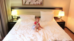 Little girl jumping on the bed in hotel. Full HD. 1920x1080 Stock Footage