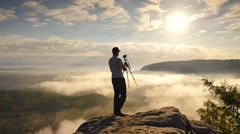 Photographer finished work and folding camera and tripod.  Dreamy fogy landscape Stock Footage