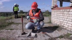 Construction worker divides brick with hammer Stock Footage