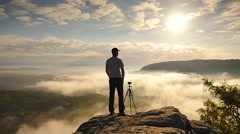 Photographer preparing tripod on cliff. Dreamy fogy landscape, misty sunrise Stock Footage