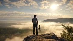 Photographer preparing tripod on cliff. Dreamy fogy landscape, misty sunrise - stock footage