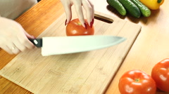 Female hands cutting red tomato on the wooden cutting board Stock Footage