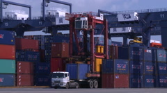 A straddle carrier picking up a container of a truck in Port of Kaohsiung Stock Footage