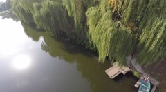 Weeping willow trees reflected on a river. drone video Stock Footage