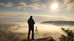 Photographer stay at camera on tripod close to cliff edge. Dreamy fogy landscape Stock Footage