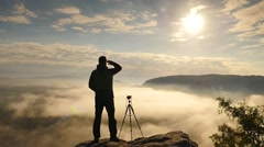 Dreamy job. Photographer in outdoor wearing  at camera on tripod on rock Stock Footage