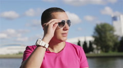 A young man putting off his sunglasses and talking into the camera Stock Footage