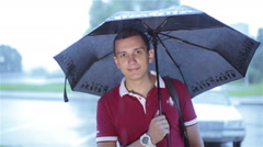 A young man with an umbrella smiling Stock Footage
