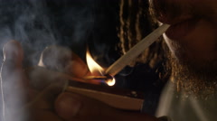 Close up of male lighting a roll up cigarette and smoking, in slow motion Stock Footage