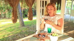 Woman sitting at the summer cafe and using her smartphone 2 Stock Footage