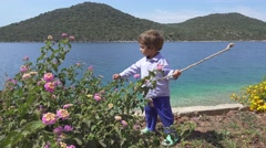 Small boy culls flowers against beautiful sea view Stock Footage
