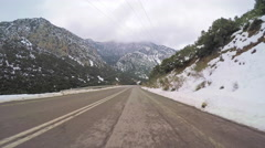 POV car mount vehicle driving road winter rural snow cloudy sky mountain Stock Footage