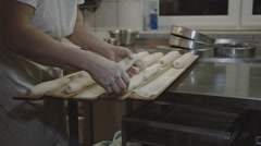 Baker puts Bread on wooden Boards Stock Footage