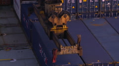 The spreader of a gantry crane is unloading a container of a large ship. Stock Footage