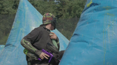 Paintballplayer on the Field while a Battle is going on Stock Footage