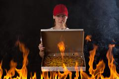 Young girl with pizza box on fire Stock Photos