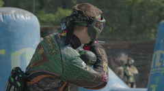 Paintballplayer on the Field while a Battle is going on in Slow Motion Stock Footage