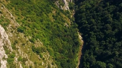 Beautiful high aerial view of a small river with dense trees on hillside Stock Footage