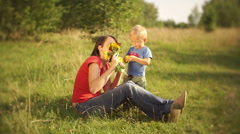 Pretty young mother with a young son happily playing with flowers outdoors Stock Footage