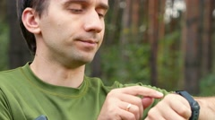 Young man touches the wearable in a park. Green T-shirt. Read the message and Stock Footage