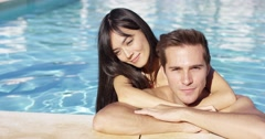 Handsome smiling couple cuddles in swimming pool Stock Footage