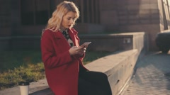 Business Woman in red coat seated near business center and using Mobile Phone Stock Footage