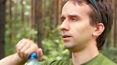 Young male cyclist drinks water from a bottle. Green T-shirt, close-up Stock Footage
