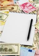 Opened spiral notepad sheet in a cage on money background Stock Photos