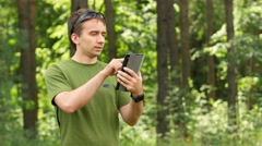 Young man touching tablet in the park among the trees. Green T-shirt and Stock Footage