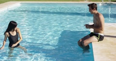 Girlfriend splashing her boyfriend at pool Stock Footage