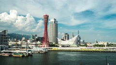 View of Kobe bay with Port Tower, dynamic clouds on blue sky and boat. 4K Stock Footage
