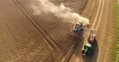Aerial shot of a combine harvester pumping wheat on a trailer Stock Footage