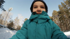 ACTION CAM: Portrait of a cute little boy rides on a sledge in a park in winter Stock Footage