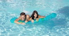 Joyful couple swimming together on floatie in pool Stock Footage