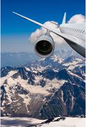 Plane flying over the snow-capped mountains Stock Photos