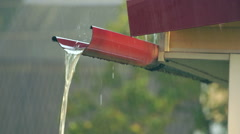 Water runs down the gutter along the roof in heavy rain Stock Footage