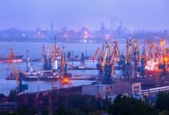 Sea commercial port at night against working steel plant Stock Photos
