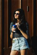 Sexy and pretty brunette in sunglasses with coffee in hand Stock Photos