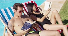 Relaxed attractive young couple reading poolside Stock Footage