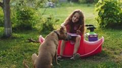 Little Girl Feeding the Dog in the Garden Stock Footage