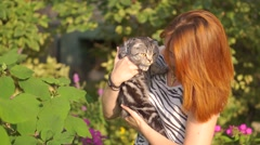 Young woman with scottish-fold cat outside Stock Footage