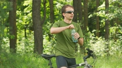 Young male cyclist drinks water from a bottle in the park. Green T-shirt and Stock Footage