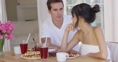 Woman trying to feed annoyed man a waffle Stock Footage